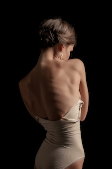 Una mujer hermosa, vista posterior sobre fondo oscuro