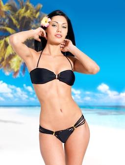 Mujer con hermoso cuerpo en bikini negro tomar el sol en la playa