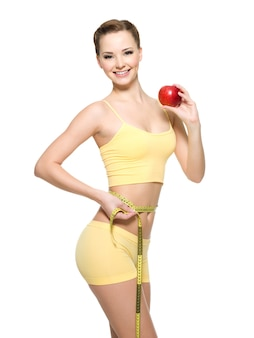 Mujer con hermoso cuerpo deportivo delgado midiendo la línea de la cintura y sosteniendo una manzana roja fresca. retrato aislado en blanco