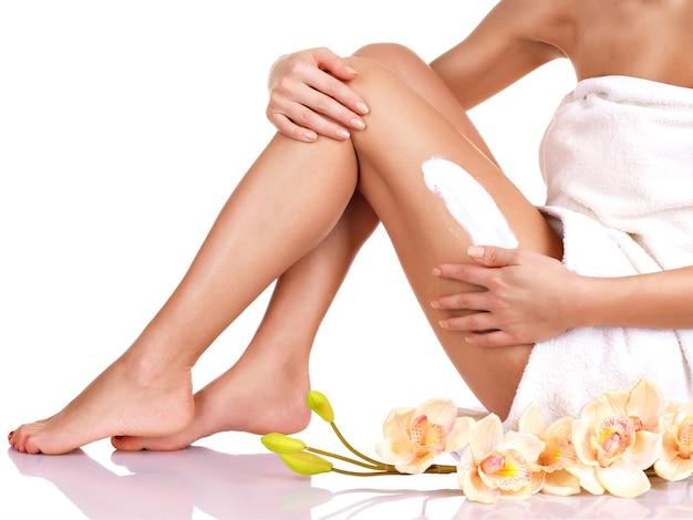 Mujer con un hermoso cuerpo usando una crema en la pierna sobre un fondo blanco.