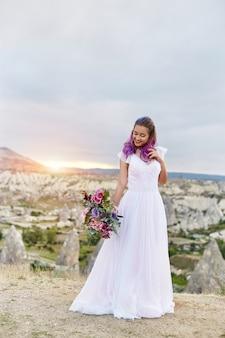 Mujer con un hermoso ramo de flores en sus manos se encuentra en la montaña en los rayos del sol al atardecer. hermoso vestido largo blanco en el cuerpo de la niña. novia perfecta con cabello rosado