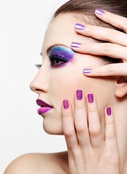Mujer con hermoso rostro y estilo de moda maquillaje y belleza manicura púrpura de uñas