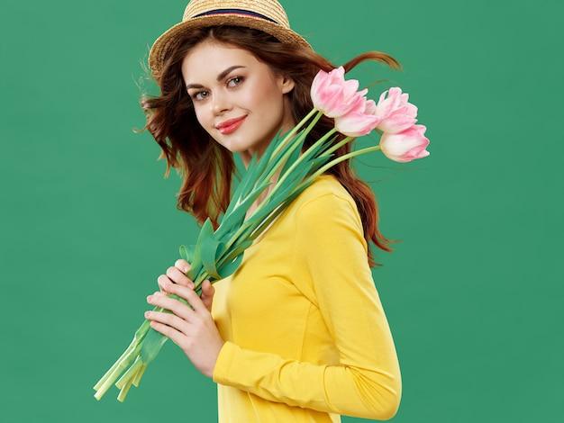 Mujer con un hermoso vestido con flores el 8 de marzo, flores de regalos iluminan el estudio de san valentín