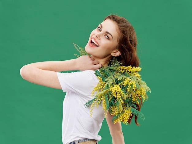 Mujer en un hermoso vestido con flores el 8 de marzo, regalos flores superficie ligera estudio de san valentín