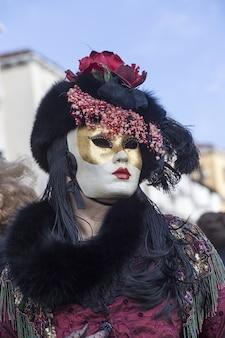 Mujer con un hermoso vestido y una máscara tradicional de venecia durante el carnaval de fama mundial