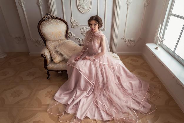 La mujer en un hermoso vestido rosa y capa rosa.