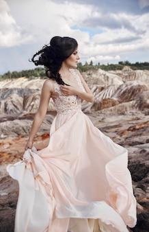 Mujer en un hermoso vestido rosa en las montañas fabulosas.
