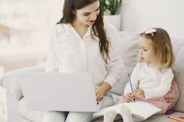 Mujer con hija usando la computadora portátil