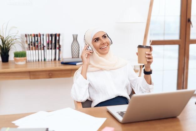 Mujer en hijab escucha música en auriculares