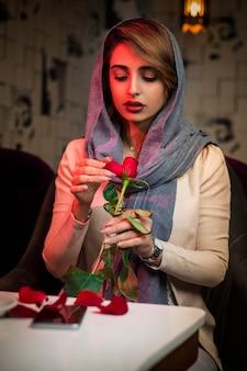 Mujer en hijab con una rosa en restaurante