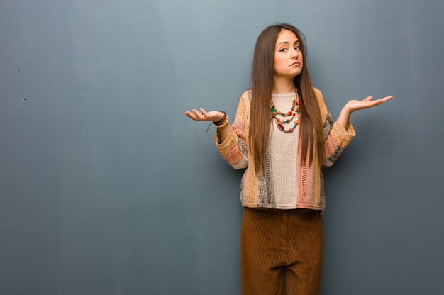 Mujer hippie joven dudando y encogiéndose de hombros.