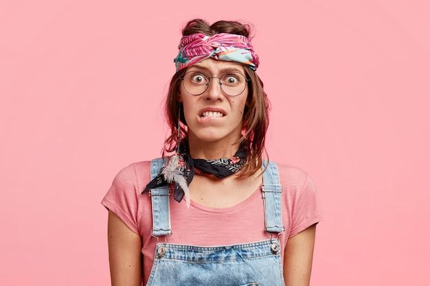 La mujer hippy nerviosa perpleja muerde los labios inferiores, mira avergonzada, se preocupa antes de un evento importante, usa un elegante pañuelo y un mono