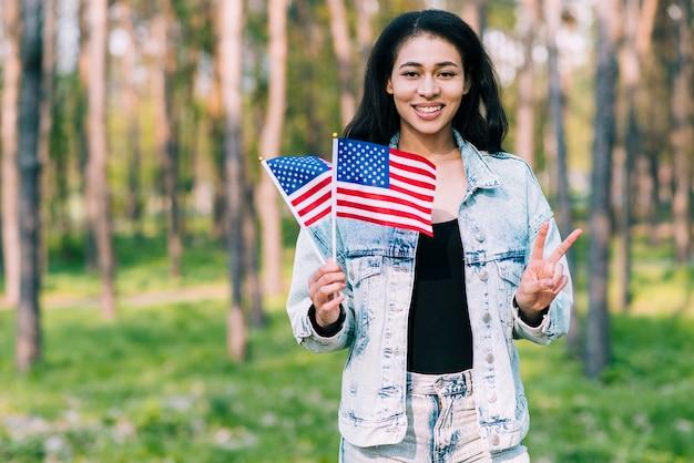 Mujer hispana con banderas de estados unidos mostrando gesto de paz.