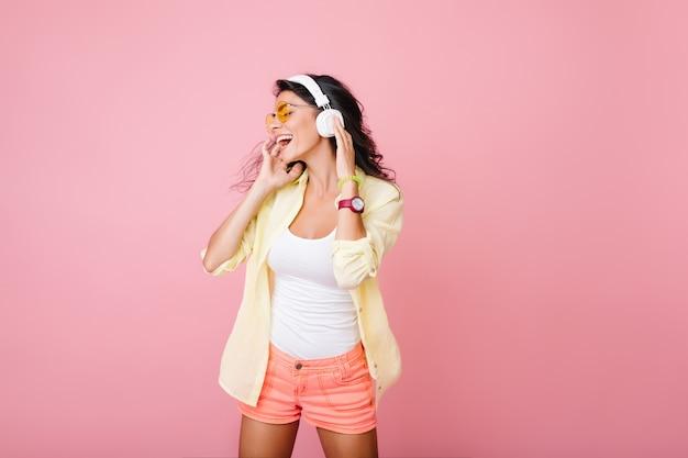 Mujer hispana despreocupada en pantalones cortos de color rosa cantando mientras posa. retrato de interior de una chica asiática de moda en la tapa del tanque blanca tocando auriculares y mirando a su alrededor.