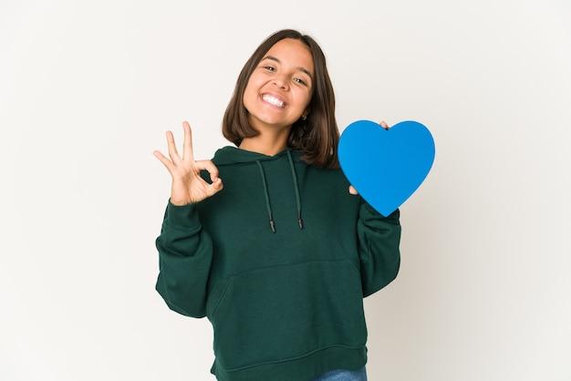 Mujer hispana joven que sostiene una forma de corazón alegre y confiada que muestra el gesto aceptable.