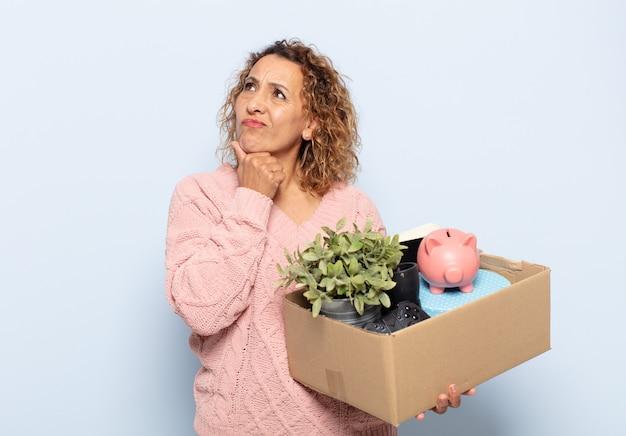 Mujer hispana de mediana edad pensando, sintiéndose dudosa y confundida, con diferentes opciones, preguntándose qué decisión tomar