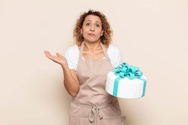 Mujer hispana de mediana edad que se siente perpleja y confundida, dudando, ponderando o eligiendo diferentes opciones con expresión divertida