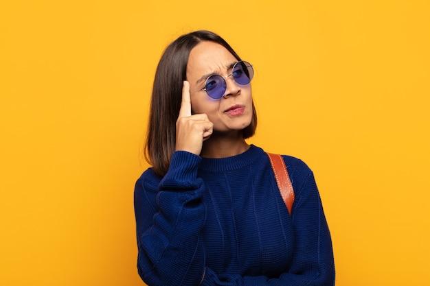 Mujer hispana con mirada concentrada, preguntándose con expresión dudosa, mirando hacia arriba y hacia un lado