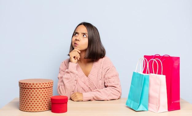 Mujer hispana pensando, sintiéndose dudosa y confundida, con diferentes opciones, preguntándose qué decisión tomar