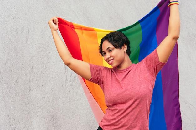 Mujer hispana de pie en la calle con la bandera lgtb. concepto lgbt