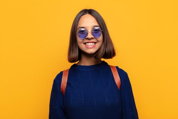 Mujer hispana que parece feliz y tonta con una sonrisa amplia, divertida y chiflada y los ojos bien abiertos