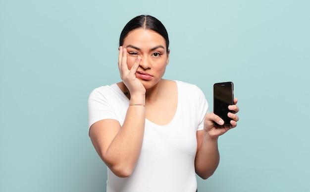 Mujer hispana que se siente aburrida, frustrada y somnolienta después de una tarea aburrida, aburrida y tediosa.