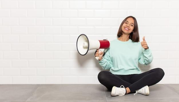 Mujer hispana que se siente orgullosa, despreocupada, segura y feliz, sonriendo positivamente con los pulgares hacia arriba