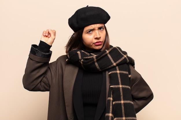Mujer hispana que se siente seria, fuerte y rebelde, levanta el puño, protesta o lucha por la revolución