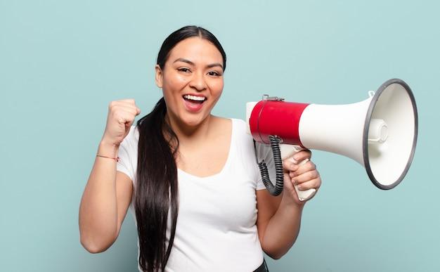 Mujer hispana que se siente sorprendida, emocionada y feliz, riendo y celebrando el éxito, diciendo ¡guau!