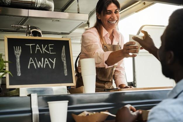 Mujer hispana que sirve comida para llevar dentro del camión de comida - centrarse en la cara del camarero