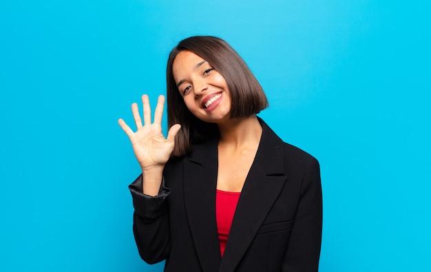 Mujer hispana sonriendo y mirando amigablemente, mostrando el número cinco o quinto con la mano hacia adelante, contando hacia atrás