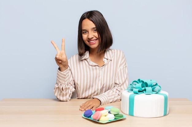 Mujer hispana sonriendo y mirando amigablemente, mostrando el número dos o el segundo con la mano hacia adelante, contando hacia atrás
