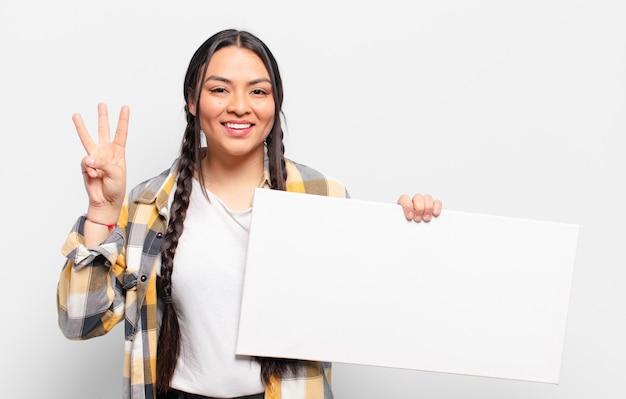 Mujer hispana sonriendo y mirando amistosamente, mostrando el número tres o tercero con la mano hacia adelante, contando hacia atrás