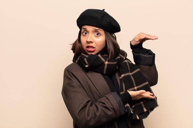 Mujer hispana sosteniendo un objeto con ambas manos en el espacio de copia lateral, mostrando, ofreciendo o publicitando un objeto