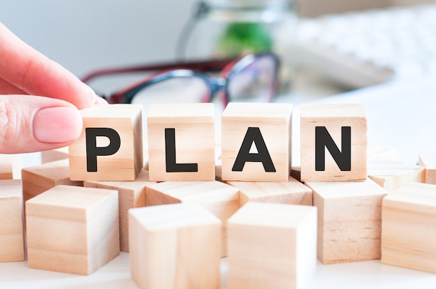 Mujer hizo palabra plan con bloques de madera. enfoque selectivo.