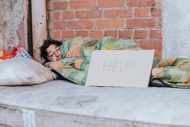 Mujer sin hogar debajo de una manta con signo de ayuda al aire libre