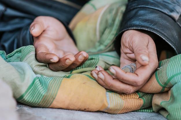 Mujer sin hogar sosteniendo las manos en busca de ayuda