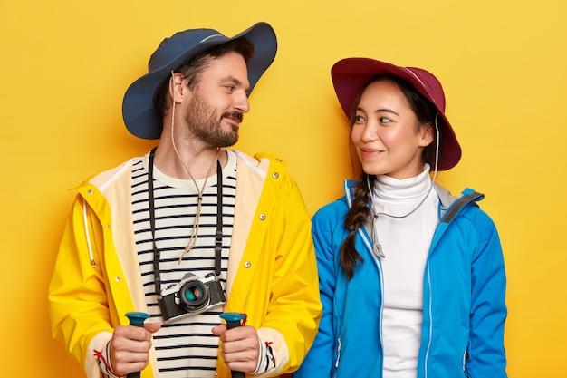 La mujer y el hombre activos diversos se miran con alegría el uno al otro, usan impermeable y chaqueta, sombreros, exploran un nuevo lugar