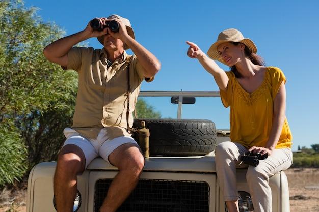 Mujer con hombre apuntando mientras está sentado en el capó del vehículo