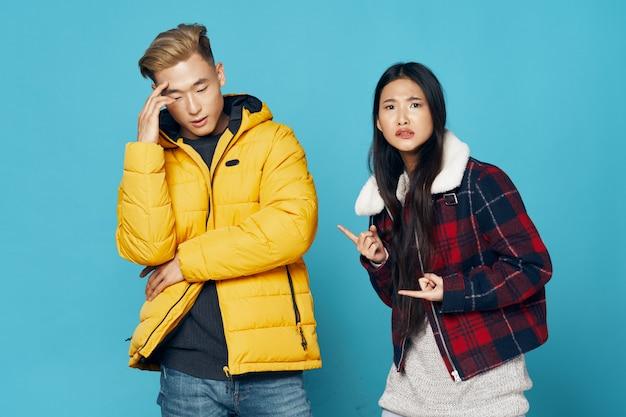 Mujer y hombre asiáticos en pared de color brillante posando modelo juntos