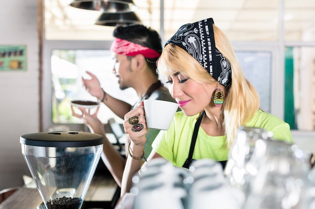 Mujer y hombre barista en café asiático preparando café