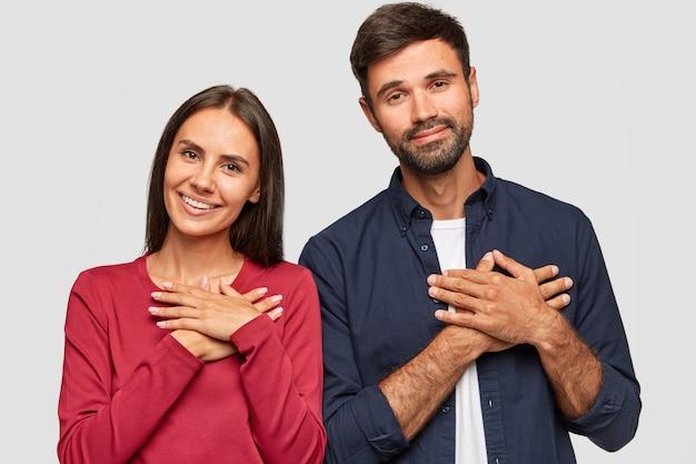 La mujer y el hombre caucásicos positivos mantienen las manos en el pecho, expresan gratitud, permanecen de pie cerca, tienen expresiones felices y amistosas