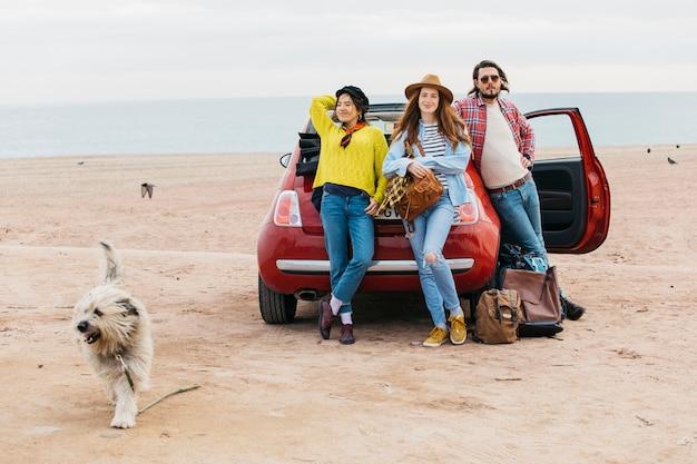 Mujer y hombre cerca de carro y perro corriendo en la playa.