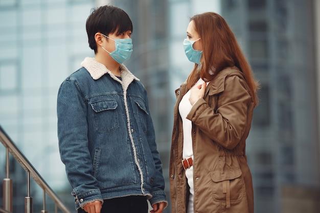 Una mujer y un hombre chino llevan máscaras protectoras