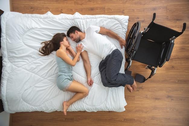 La mujer y un hombre discapacitado tendido en la cama. vista desde arriba
