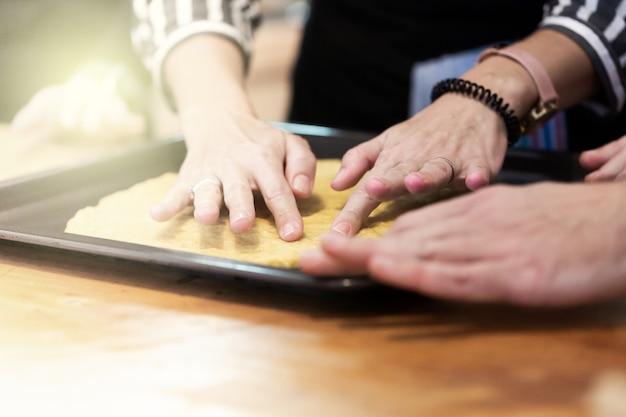 La mujer y el hombre le enseñan a sus amigos cómo cocinar alimentos: piza o pastel. gente cocinando en la cocina juntos. clase magistral culinaria