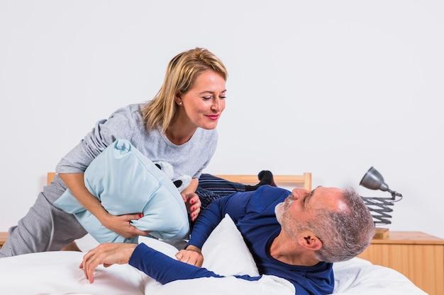 Mujer y hombre envejecidos que se divierten con las almohadas y que mienten en cama