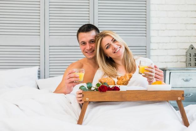 Mujer y hombre felices con los vidrios en cama cerca de la comida en la mesa de desayuno