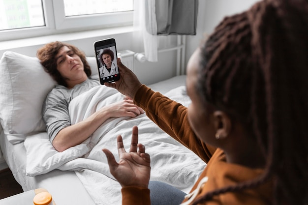 Mujer y hombre hablando con un médico por videollamada.