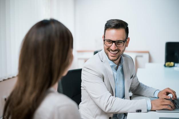 Mujer y hombre hablando durante la reunión de negocios
